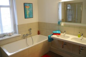 Modernes Bad mit Dusche, Wanne, Doppelwaschtisch und WC